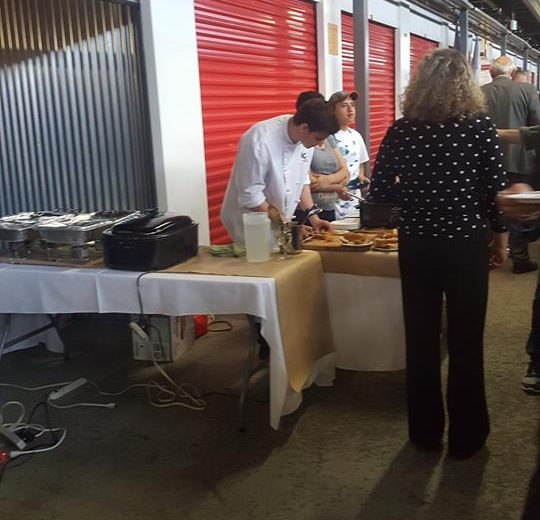 Flavours of Thorncliffe, people serving food in a storage facility, red storage units in the background