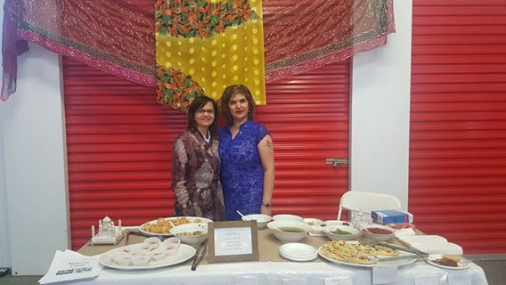 Flavours of Thorncliffe, two women standing behind a white rectangular table with several plates of food on top, two red storage units in th eback