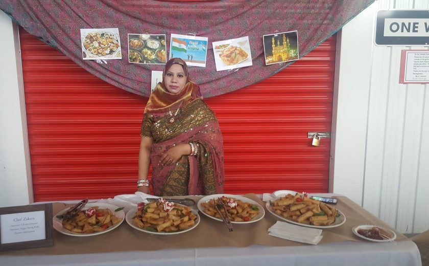 Flavours of Thorncliffe, woman standing in front of 4 plates of spring rolls, red storage unit in the background
