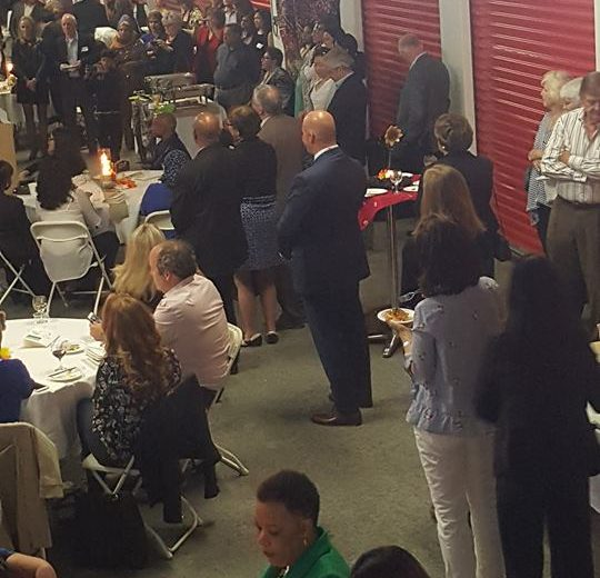 Flavours of Thorncliffe, large group of people inside storage facility eating at round tables, red storage units in the back
