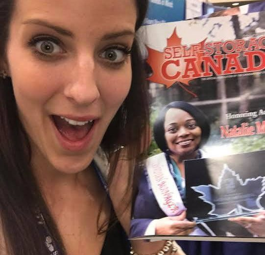 2017 Spring Conference & Trade Show, woman with long brown hair taking a selfie with a magazine titled Self-Storage Canada smiling