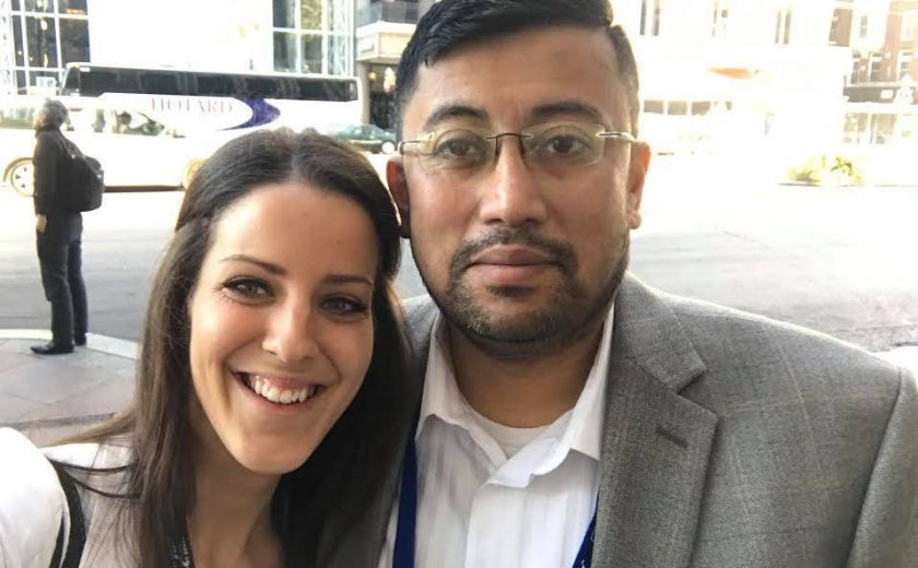 2017 Spring Conference & Trade Show, a man and a woman taking a selfie outside with a building with a lot of windows in the background, both wearing white shirts, man wearing a grey blazer and glasses