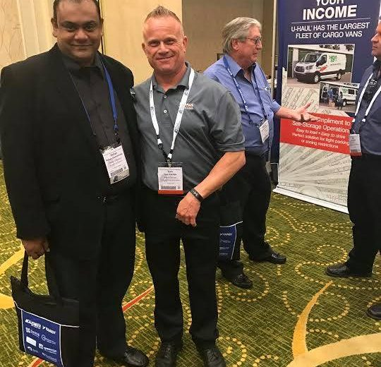 2017 Spring Conference & Trade Show, two men smiling wearing grey shirts and black pants, two other men in the background talking with a U-Haul Increase Your Income backdrop in the background