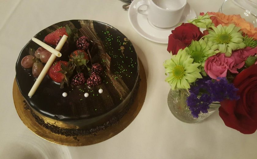 dark chocolate cake with berries and grapes on top, colourful flowers on the right side in a glass jar, white teacup on a white plate behind the cake and flowers