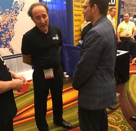 2017 Spring Conference & Trade Show, two men talking at a booth, Storage Auction Website backdrop in the background with a map