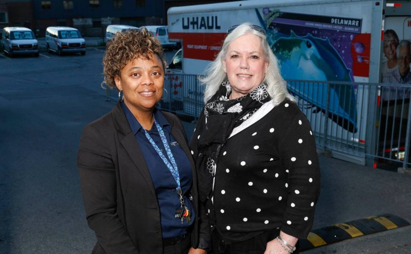 two women smiling, one is wearing a blue shirt with a black jacket, other is wearing a black and white polka dot shirt, U-Haul trucks parked