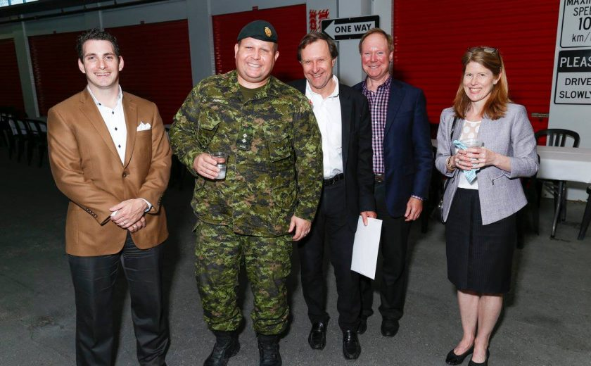 group of five nicely dressed up, one of the five is wearing a green uniform, red storage units in the background