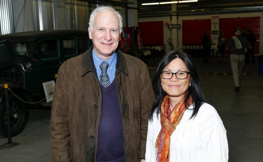 a man wearing a purple sweater vest, blue shirt and brown jacket standing next to woman wearing a white sweater with black glasses, old car green car on display, storage units with red doors in the background