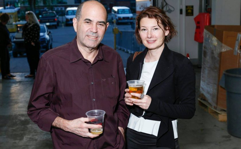 man wearing maroon shirt and woman wearing white shirt with black jacket, inside self storage facility, parking lot filled with cars in the background