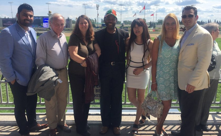 Woodbine Races, group of 8 people taking a picture in front of the race track