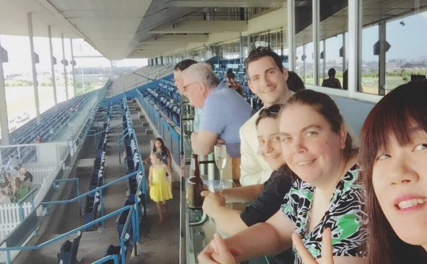 Woodbine Races, group selfie of 4 people outdoors at the race track, several rows of blue chairs in the background, under a cement roof