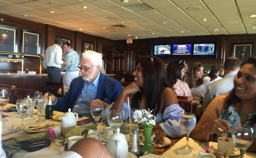 Woodbine Races, tables of people eating food and drinking, dark brown walls with three TV's and picture frames hanging