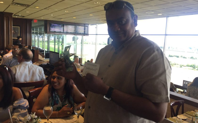 Woodbine Races, man smiling inside in the brown dining area, wearing dark sunglasses on head, holding money