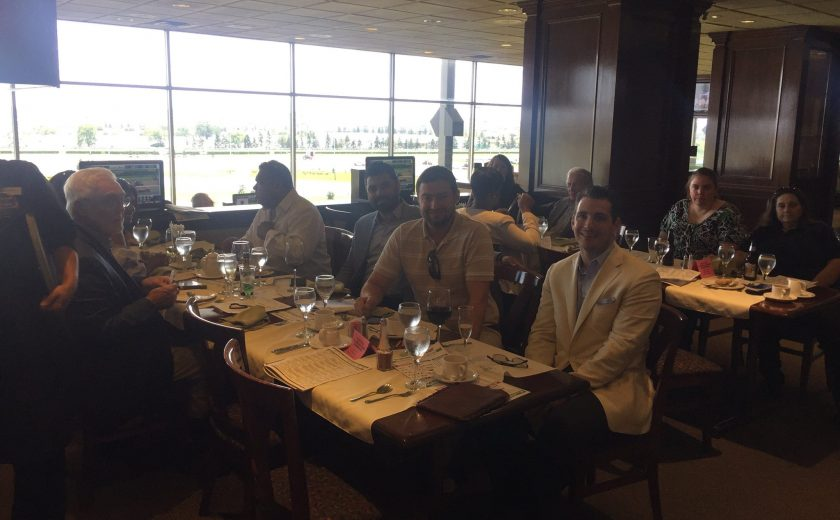 Woodbine Races, group photo of everyone sitting at the tables, brown chairs and tables, bright large window in the background