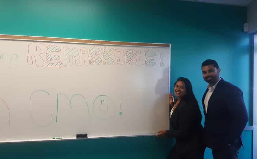 Man and woman wearing white dress shirt and black blazer standing on the right side of a large whiteboard in the Client Management Office, teal coloured wall as the background