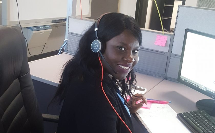 Women wearing black and a headset in front of a computer in the client management office, pink and green balloon in the background