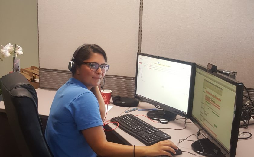 Woman wearing a blue t-shirt in front of two desktop computers in the client management office, yellow, red, white and purple balloon in the background