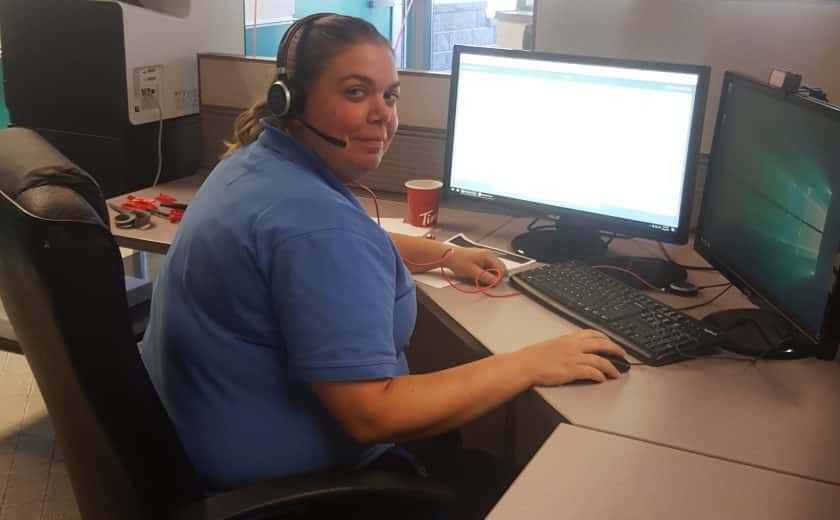 Woman wearing a blue t-shirt and headset in front of two computers, doors and windows in the background, white and green balloon in background