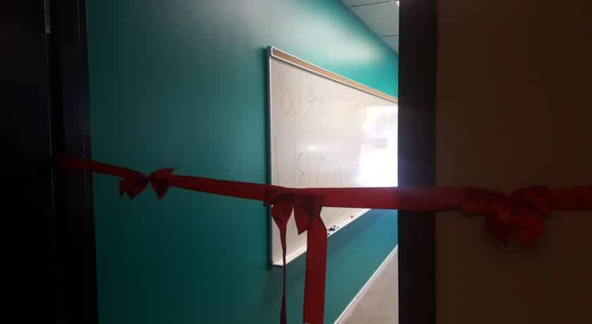 long red ribbon with three bows across open client management office door, teal coloured wall with whiteboard hanging