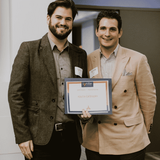 two men standing wearing a buttoned up shirt and a blazer with black pants smiling at camera holding ignite certificate