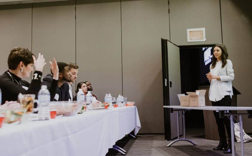 five people sitting at the judges panel behind a white long table listening to a young woman wearing white present at ignite capital pitch competition