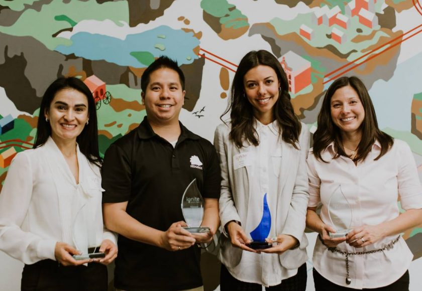 three women and one man standing with clear and blue trophies from ignite capital pitch competition, women are wearing white and pink blouses, man wearing black t-shirt, colourful design on the wall