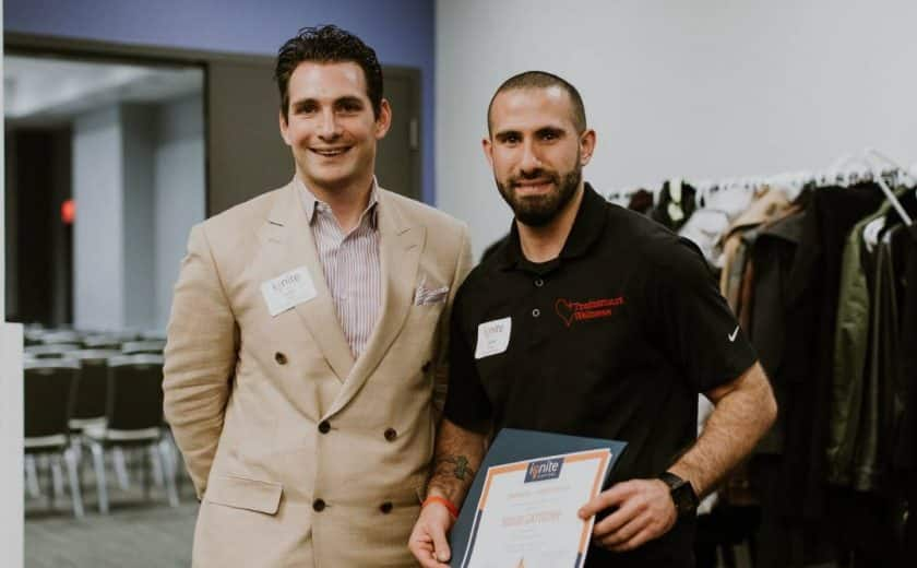 Two men standing smiling at the camera, one is wearing a striped shirt with light brown blazer jacket, the other man is wearing a black shirt holding an ignite capital certificate, jackets hanging on a rack in the background