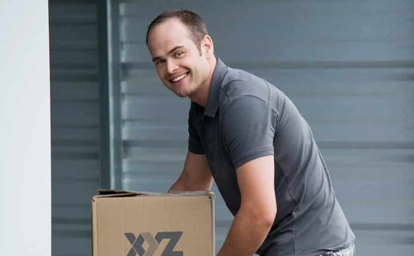man wearing grey t-shirt holding XYZ Storage moving boxes