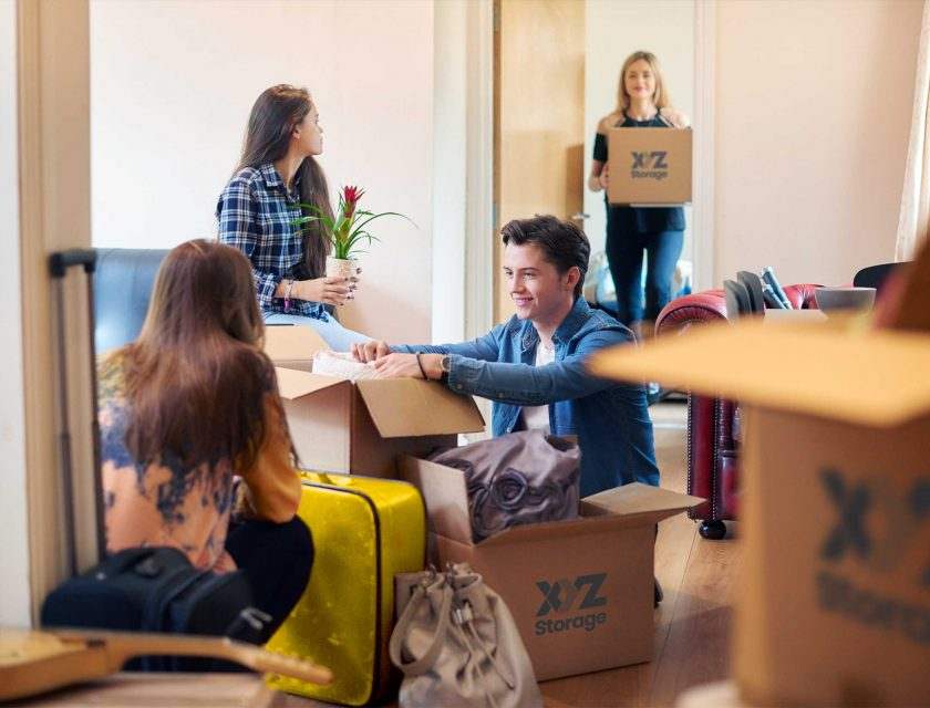 boy and girl on the floor packing their apartment with XYZ Storage moving boxes, one girl sitting on a couch holding a plant, another girl standing holding an XYZ Storage moving box