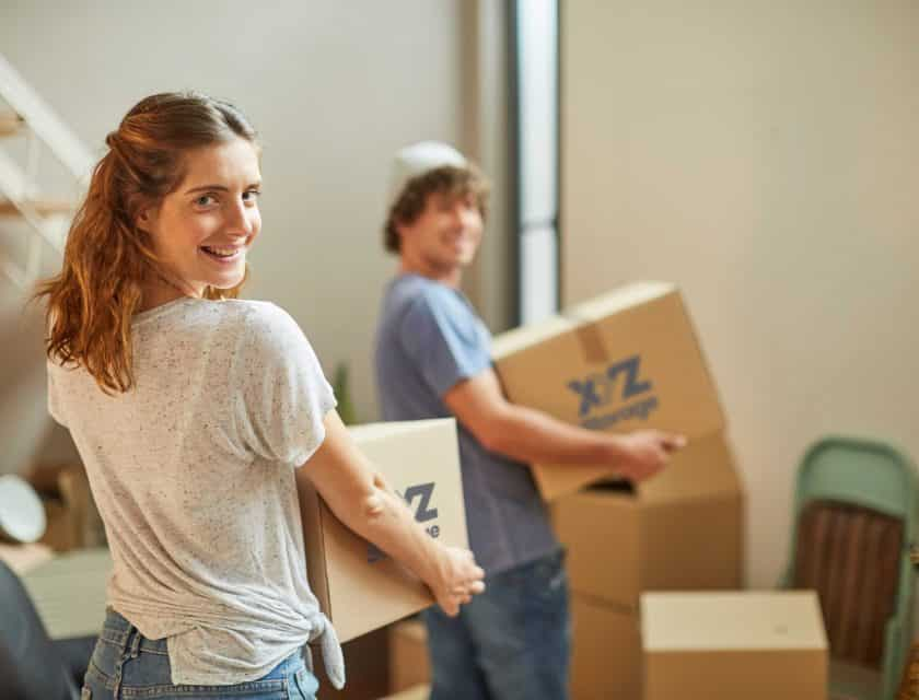 boy wearing a blue t-shirt and girl wearing white t-shirt holding XYZ Storage moving boxes