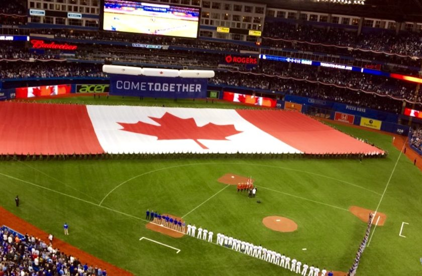 full baseball stadium filled with people, large red and white Canadian flag with the red maple leaf in the middle, baseball players lined up