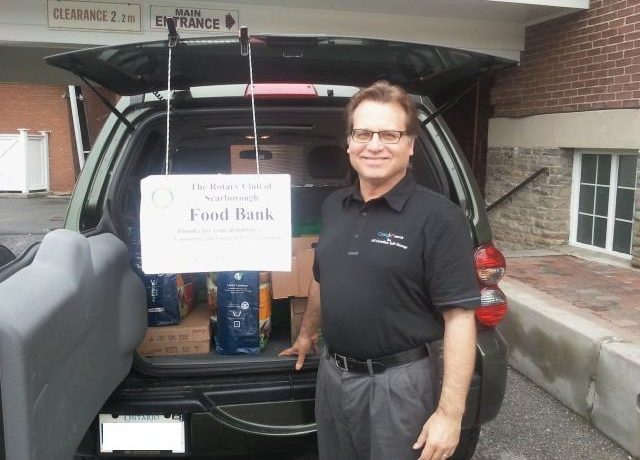 Man standing in front of open car trunk at the Rotary Club of Scarborough Food Bank event