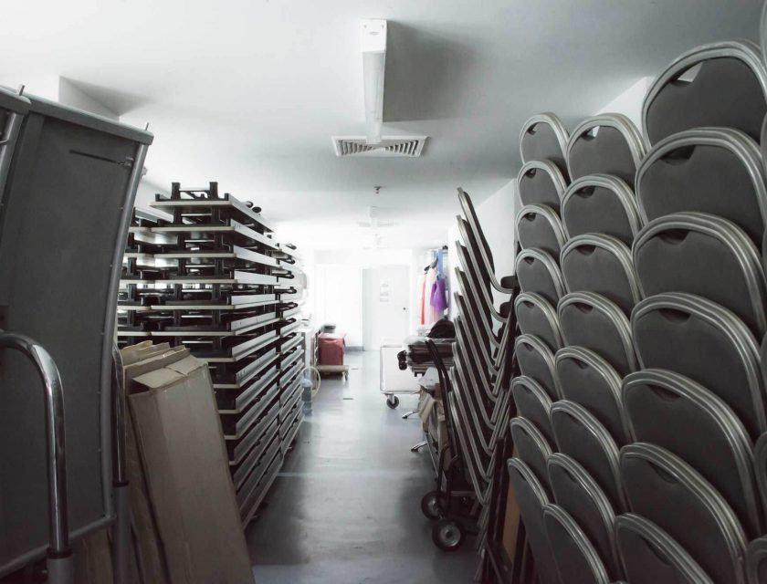 white storage room with multiple black chairs, tables, boxes, and colourful clothes on a hanger in the back