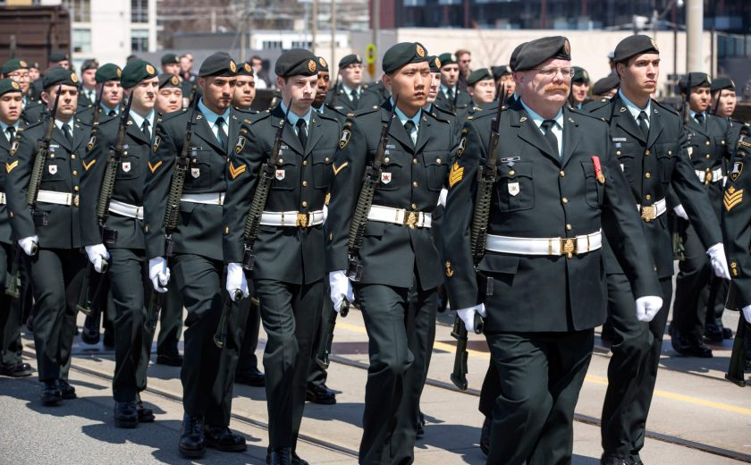 Group of men walking the city streets, wearing a black military uniform with a white belt, holding a long gun