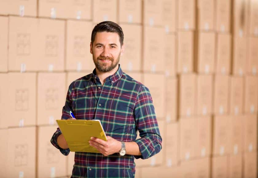 man wearing a colourful plaid shirt holding a yellow clipboard a blue and white pen, wall of brown boxes in the background