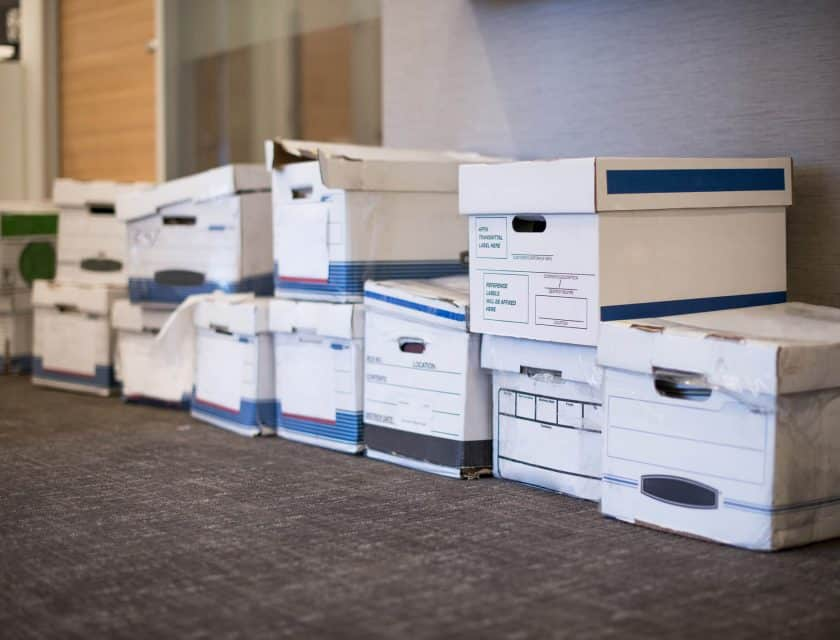 several white boxes filled with business files aligned on the floor