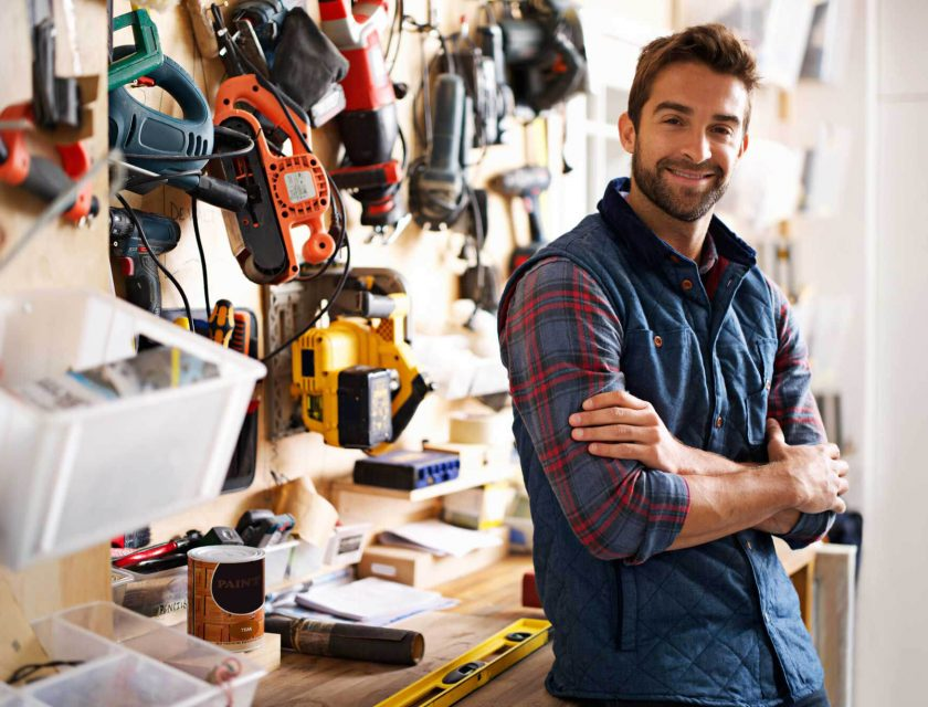 man wearing a blue and red plaid shirt and a blue vest smiling, leaning against a desk with a bunch of tools hanging on the wall