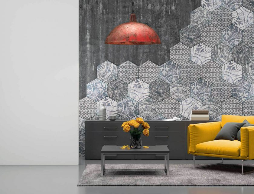 grey room with a hexagon designed wall, long dark grey dresser against the wall with brown and white book on top, yellow armchair with grey pillows, coffee table with yellow flowers, a red and brown ceiling light