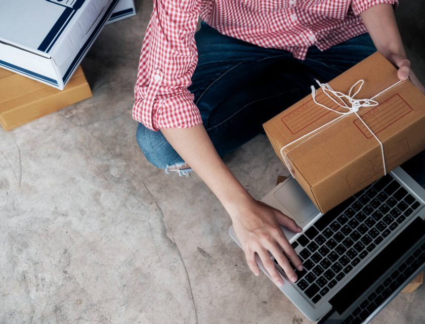 person wearing a red and white plaid shirt and blue jeans, holding a brown package with a white string, typing on a laptop
