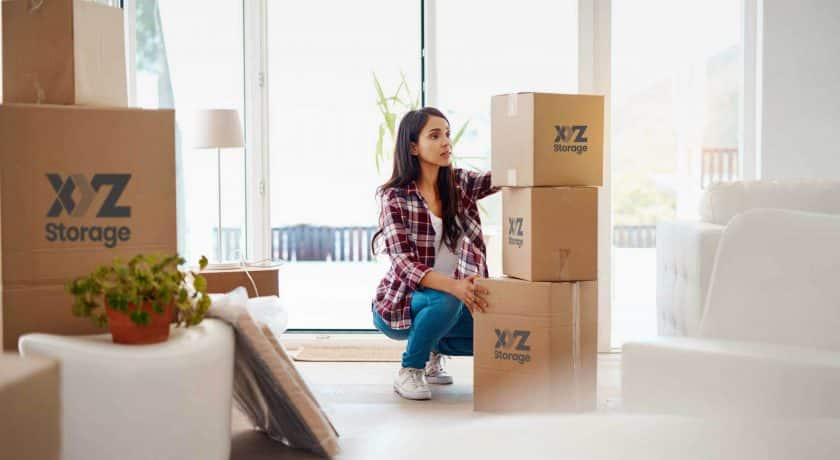 young woman wearing a plaid shirt with blue jeans and white shoes, packing her belongings using XYZ Storage boxes