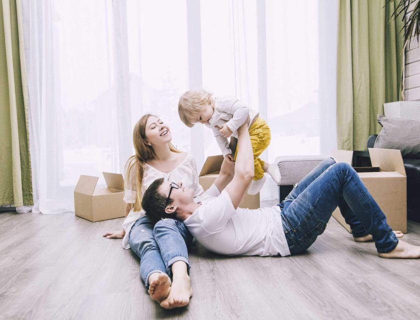 family of three laying on the floor in a house surrounded by brown boxes and a big window in the background