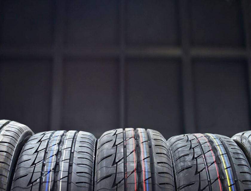 black background, five tires in the front with thin blue, yellow, white, and red stripes