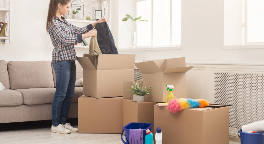 lady wearing plaid shirt and blue jeans packing belongings in brown boxes in white room