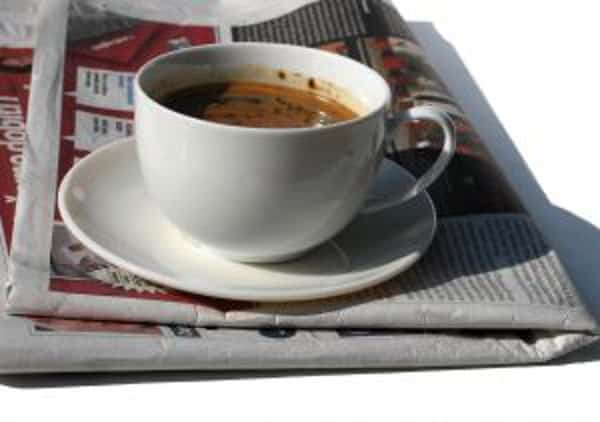 white coffee cup on a white plate on top of a newspaper