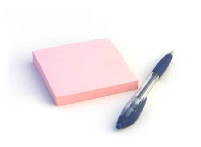 pink sticky note pad with a blue pen beside it
