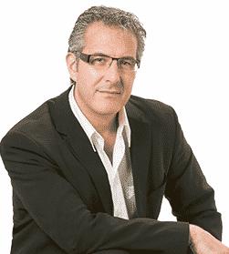 Man sitting wearing glasses, a white dress shirt and a black blazer