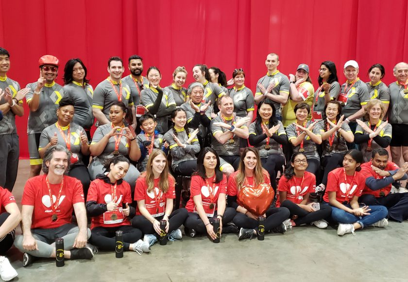 XYZ Storage team taking a group picture wearing yellow, grey, white, and red colours, in front of a red curtain