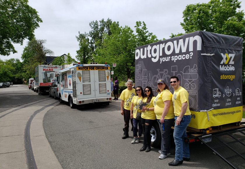 XYZ Storage team wearing grey and yellow standing in front of large grey and yellow mobile storage container, white ice cream truck in front, green trees in the background