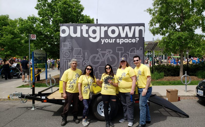 XYZ Storage team wearing yellow and grey standing in front of white and grey mobile storage container, standing in front of a park with children and green trees