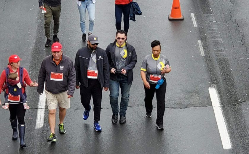 XYZ storage team walking on the highway, wearing grey, yellow, and red